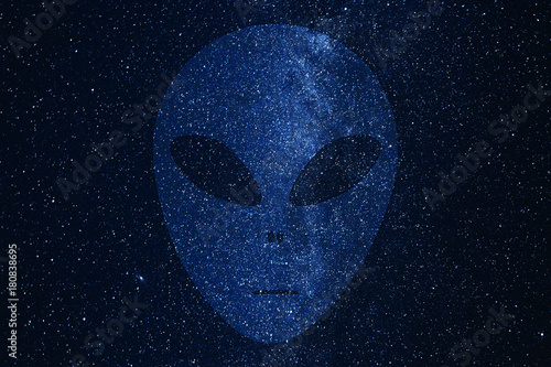 Foto op Canvas UFO Alien face silhouette on background of Milky Way galaxy with glowing stars and planets in the universe. Space sky in the night.