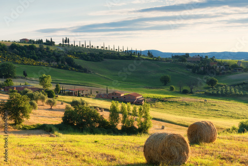 In de dag Oranje Magnificent spring landscape.Beautiful view of typical tuscan farm house, green wave hills, cypresses trees, hay bales, olive trees, beautiful golden fields and meadows.Tuscany, Italy, Europe