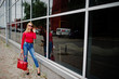 Portrait of a fabulous young woman in red blouse and jeans posing with her handbag and sunglasses outside the shopping mall on glass background.