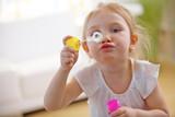 Mädchen pustet Seifenblasen im Kinderzimmer - 180847677
