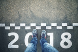 Person standing in front of a start New Year 2018 sign painted on asphalt city street. Point of view perspective used. - 180851407