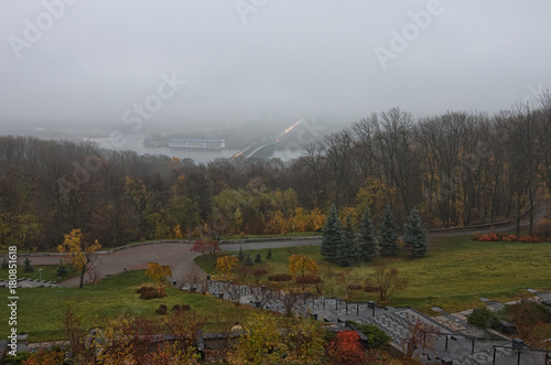 Foto op Plexiglas Kiev Mysterious foggy autumn morning. Panorama of Kyiv from the Park of Fame (Park of Glory). Metro bridge across the Dnipro river. Selective focus with wide angle lens