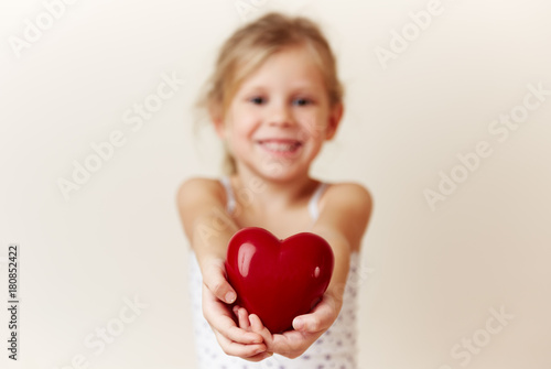 Foto Murales Beautiful smiling girl giving red heart as symbol of love and happiness.