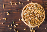 Barley grain in wooden bowl on wooden table - 180852874