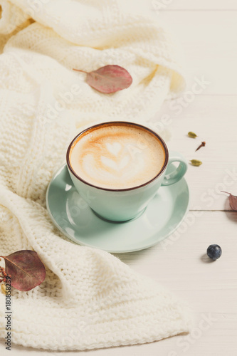 Autumn cappuccino coffee cup on white wood background