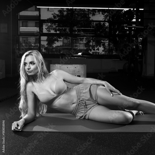 Attractive woman with long blonde hair, dressed in pink sportswear and white sneakers, lying on her stomach with legs up on green exercise mat against bright light on background and looking to left.