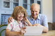 Senior Couple Sit At Home Using Digital Tablet Together
