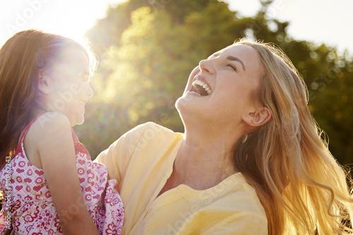 Mother Hugging Daughter Outdoors In Summer Garden