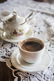 Strong Turkish style coffee in a cup on a table with sugar pot in a background