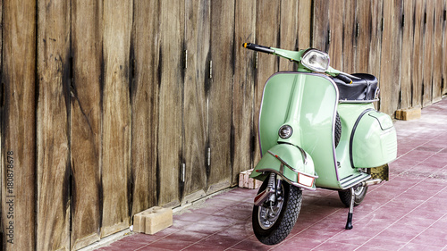 Keuken foto achterwand Scooter Green scooter against old house. wood wall mossy surface of building as background. Urban street in Thailand, Asia. Moped parked at moldy wood wall. Asian lifestyle and popular transport.