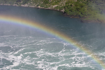 Rainbow over a river with waves