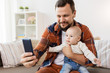 Quadro happy father with baby boy taking selfie at home