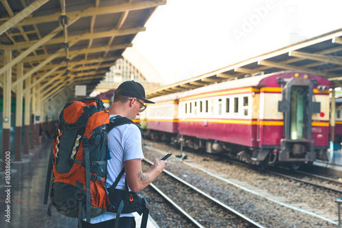 Man with a backpack waiting the train with smart phone in his hand