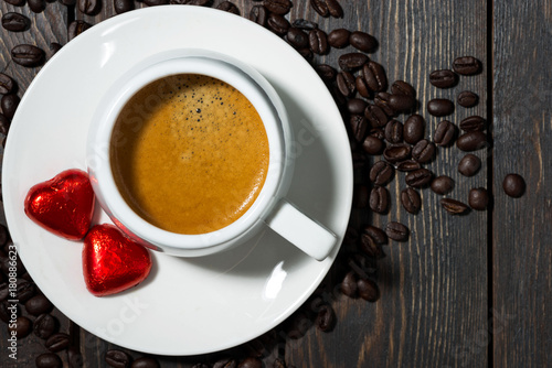 cup of espresso and chocolate sweets in the form of a heart, top view