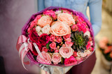 Large and gorgeous pink bouquet of flowers with a succulent in womans hands