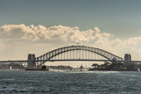 Sydney, Australia - March 26, 2017: Frontal view of black metalic Harbour Bridge including support towers on both sided seen off water under cloudscape. Denison Fort in bay and multiple small boats. - 180887692