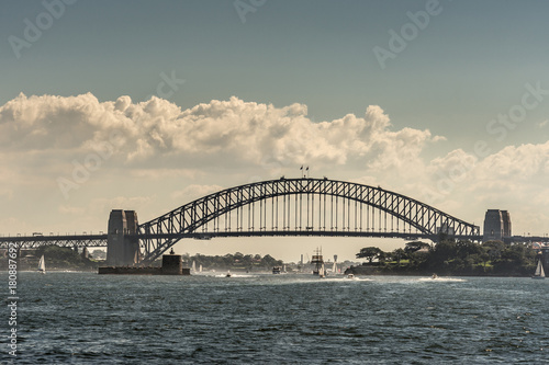 Staande foto Sydney Sydney, Australia - March 26, 2017: Frontal view of black metalic Harbour Bridge including support towers on both sided seen off water under cloudscape. Denison Fort in bay and multiple small boats.