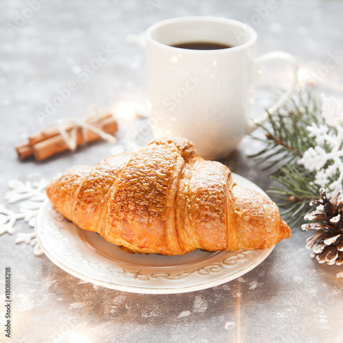 Fresh croissant and cup of hot cofffee on cosy winter background with spuce and artificial lights.