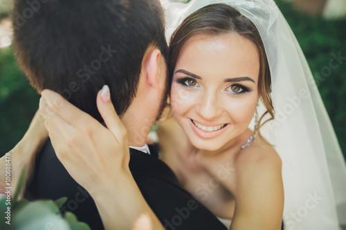 Stylish beautiful couple of happy newlyweds on their wedding day, close up portrait
