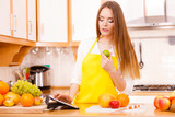 Woman housewife in kitchen using tablet