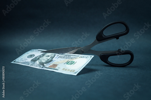 Scissors cutting a hundred dollar on a blue background.