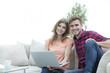 young couple of students with laptop sitting on the couch