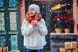 Young woman enjoying coffee or chocolate wearing white sweater, red scarf and mittens. Holidays, vacation, weekend, leisure concept.