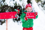 Child with letter to Santa at Christmas mail box in snow - 180896885