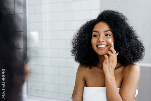 Happy young woman applying face cream with finger in bathroom