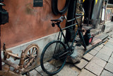 Street details in old centre of Warsaw. Black vintage bike and wooden spindle with wheel.