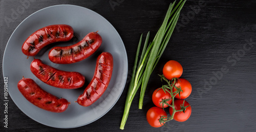 Fried sausages on a round clay plate - 180911432