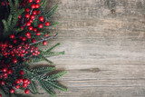 Fototapety Christmas Evergreen Branches and Berries Over Rustic Wood Background