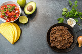 taco ingredients with roasted beef, tomatoe salsa, avocado and herbs on a dark stone background, copy space, top view from above - 180917245
