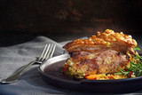 juicy roast pork with crunchy crust, rosemary and vegetables on a gray napkin against a rustic dark background, moody light, copy space - 180917843