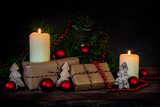 gift boxes in kraft paper and two burning candles decorated with red christmas baubles, fir branches and small wooden trees on a dark rustic background with copy space - 180917890