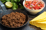 fried ground beef in a pan, as a filling for taco shells with ingredients as tomato salsa, lime and herbs on a dark stone background - 180918049