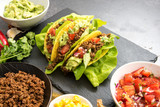 mexican tacos and some ingredients like fried ground beef, tomato salsa, guacamole, corn and herbs on a dark slate plate with copy space - 180918239
