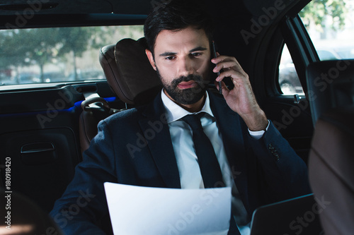 Checking report. Handsome young man talking on mobile phone and looking through documents while sitting in car