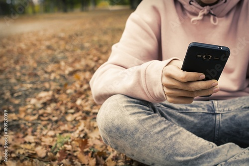 young teenager with mobile phone in the park in the fall