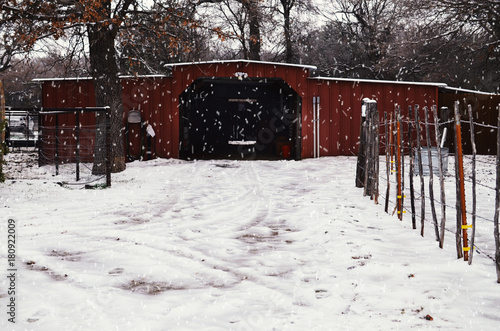 Foto op Plexiglas Bruin Rural farm winter with snow on drive to red barn, trees and nature in background of building. Snow covered cold landscape for rustic ranch Christmas.