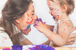 Happy mom and baby playing with painted face by paint