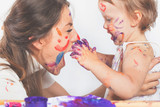 Happy mom and baby playing with painted face by paint - 180922668