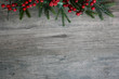 Leinwandbild Motiv Christmas Pine Tree Branches and Berries Over Rustic Wood Horizontal Background