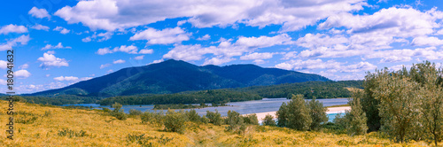 Foto op Plexiglas Purper Landscape panorama of green hills and white fluffy clouds on bright sunny day