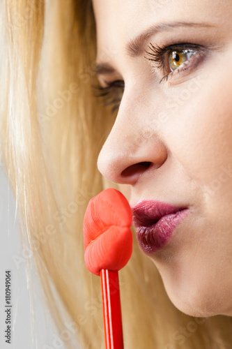 Happy woman holding fake lips on stick Poster