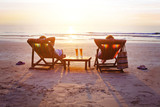 honeymoon travel, silhouettes of happy couple relaxing in deck chairs on the beach at sunset - 180951092