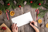 Female hand writing a letter to Santa on wooden table - 180951867
