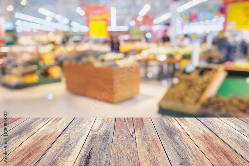 Supermarket with fresh fruits and vegetable on shelves in store blurred background - 180954812