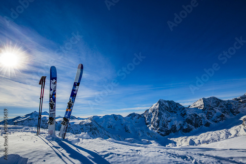 Obraz Ski in winter season, mountains and ski touring backcountry equipments on the top of snowy mountains in sunny day. South Tirol, Solda in Italy.