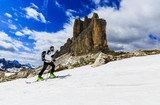 Mountaineer backcountry ski walking up along a snowy ridge with skis in the backpack. In background blue cloudy sky and shiny sun and Tre Cime, Drei Zinnen in South Tirol, Italy.   - 180955802